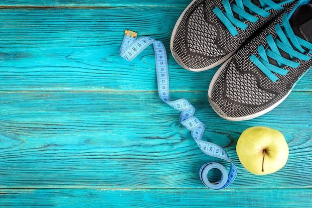 Sfondo sportivo sneakers, nastro e mela su legno blu, piatto laici