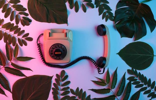 Sfondo stile retrò. telefono rotativo retrò tra foglie verdi su sfondo con luce rosa blu al neon sfumata.