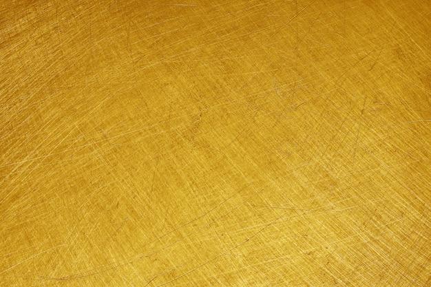 Sfondo texture metallo oro alluminio lucido giallo, graffi su acciaio inossidabile lucido.
