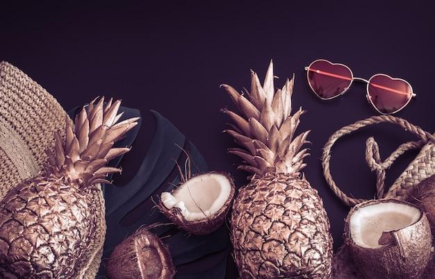 Sfondo tropicale estivo con ananas dorato e accessori estivi con occhiali a forma di cuore, su sfondo nero opaco, creatività e concetto di stile