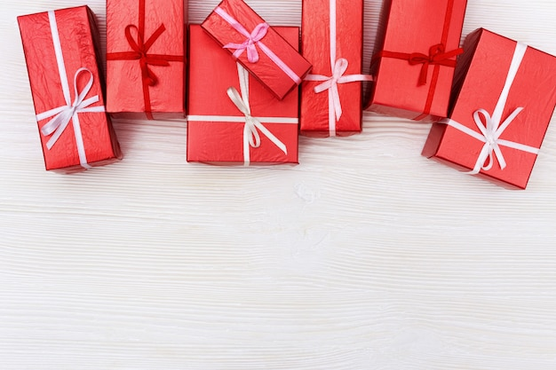 Sfondo vacanza con regali. regali rossi su legno bianco.