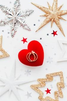Sfondo vacanza di natale con decorazioni e fedi nuziali su scatola regalo di cuore.