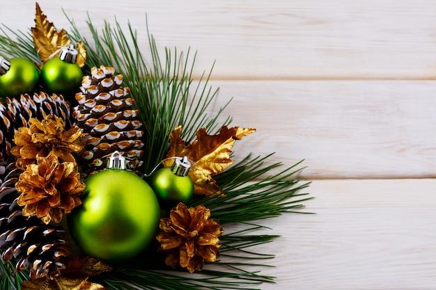 Sfondo vacanza di natale con ornamenti verdi e coni d'oro