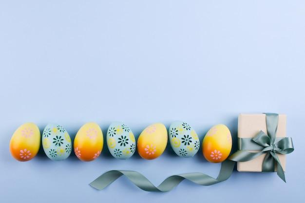 Sfondo vacanza di pasqua vista dall'alto di uova di gallina dipinte colorate disposte in fila e casella presente con nastro