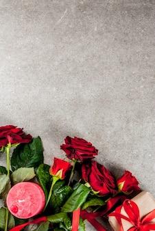 Sfondo vacanza, san valentino. bouquet di rose rosse, cravatta con un nastro rosso, con confezione regalo avvolta e candela rossa