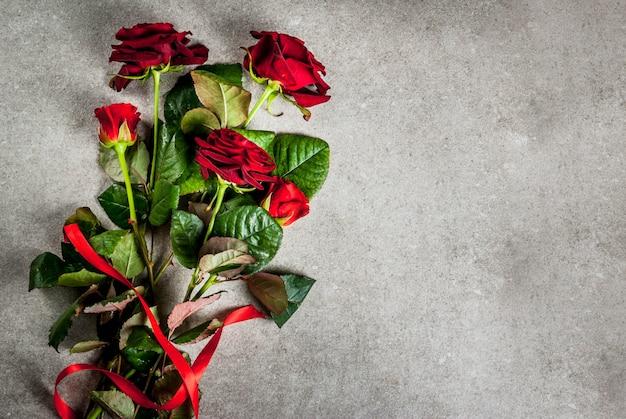 Sfondo vacanza, san valentino. bouquet di rose rosse, cravatta con un nastro rosso