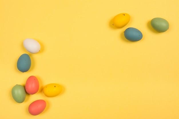Sfondo vacanze di pasqua. uova di pasqua decorate colorate su una priorità bassa gialla luminosa