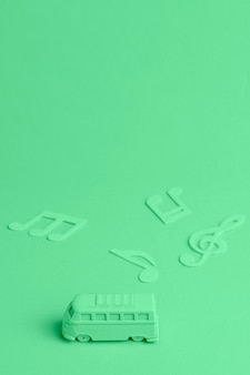 Sfondo verde con bus giocattolo e note musicali