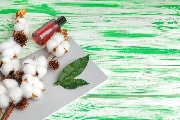 Sfondo verde con ramo di cotone, dischetti di cotone