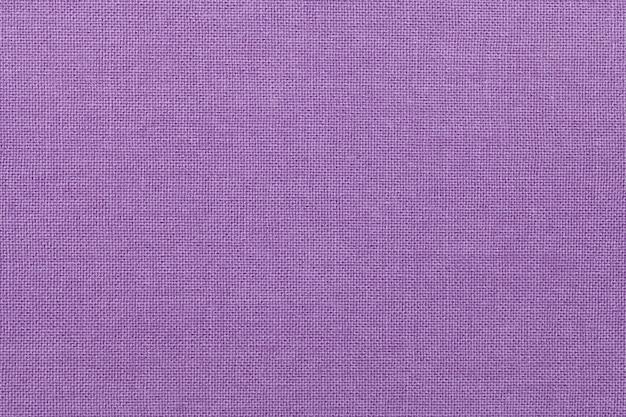 Sfondo viola chiaro da un materiale tessile. tessuto con trama naturale. scenografia.