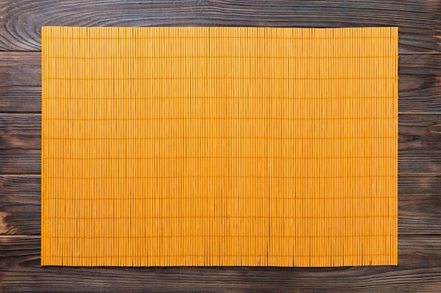 Sfondo vuoto cibo asiatico. stuoia di bambù gialla sulla vista superiore del fondo di legno con la disposizione del piano dello spazio della copia