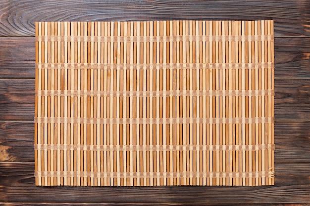 Sfondo vuoto cibo asiatico. stuoia di bambù marrone sulla vista superiore del fondo di legno con la disposizione del piano dello spazio della copia