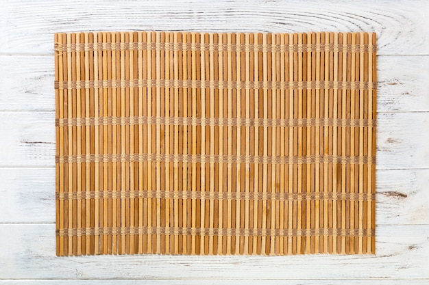 Sfondo vuoto cibo asiatico. stuoia di bambù marrone sulla vista superiore del fondo di legno wnite con la disposizione piana dello spazio della copia