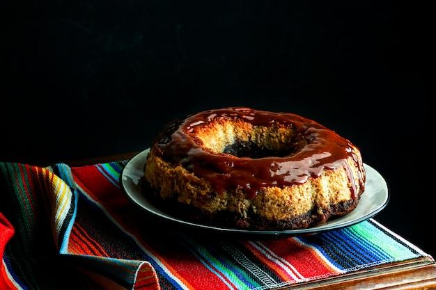 Sformato di cioccolato, chocoflan messicano, biscotto al cioccolato e budino di crema al caramello con salsa al caramello in cima, sul tavolo di legno scuro