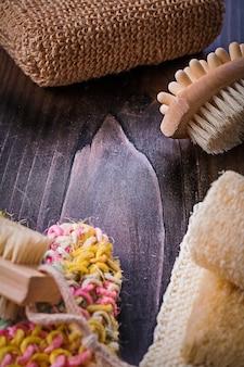 Sfrega la luffa del massaggiatore di scrubber del corpo della spazzola sul bordo di legno