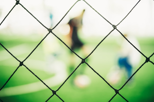 Sfuocatura della rete di addestramento di calcio sulla terra di addestramento con i bambini