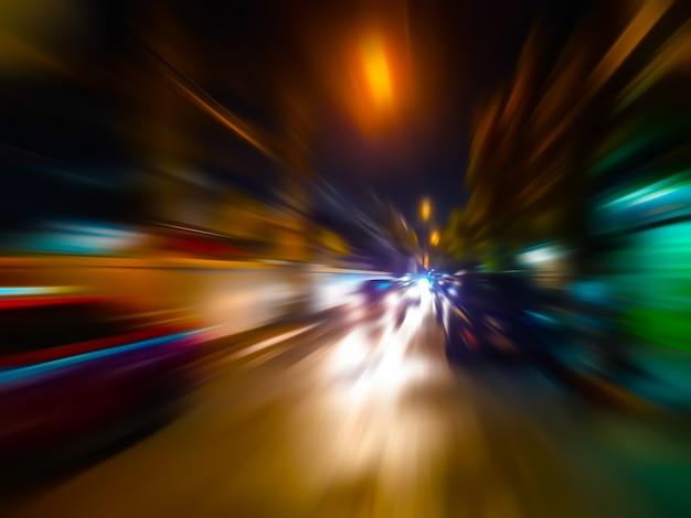 Sfuocatura di movimento astratta di velocità in città sulla luce al neon della strada di notte.