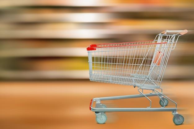Sfuocatura di movimento degli scaffali del supermercato con il carrello vuoto