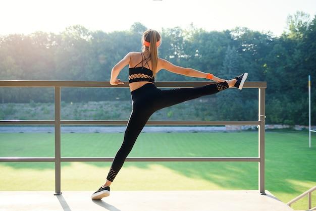 Sgirl attraente in abiti sportivi facendo esercizi di stretching per le gambe allo stadio della città.
