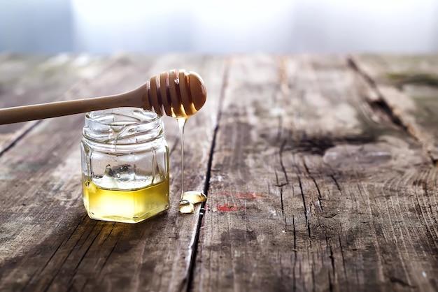 Sgocciolatura del miele da un mestolo di legno del miele in un barattolo
