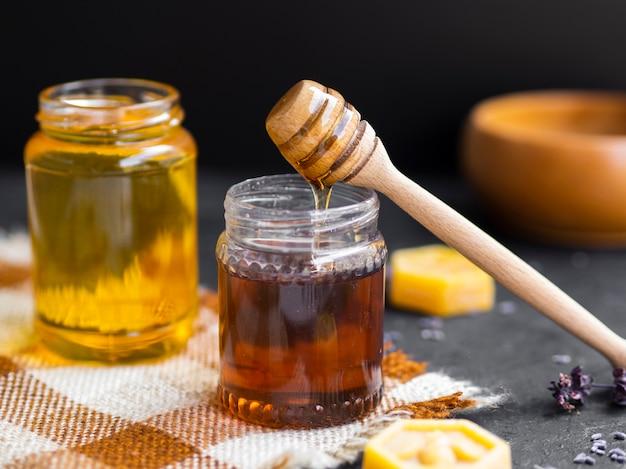 Sgocciolatura di miele in vaso di vetro