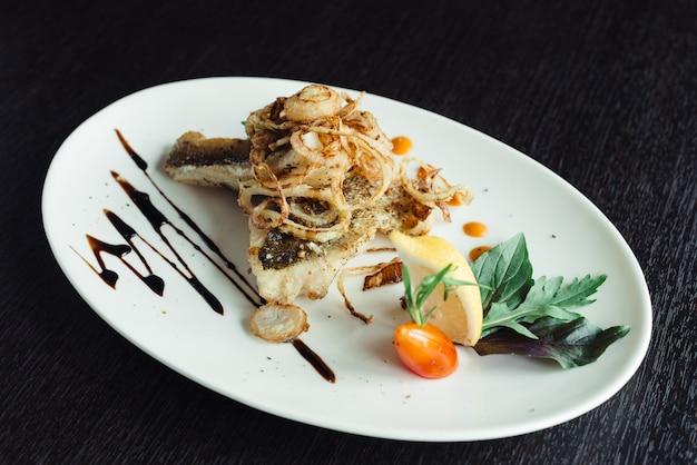 Sgombro arrostito con la cipolla sul piatto bianco sulla tavola di legno