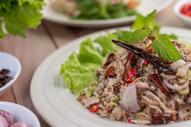 Sgombro fritto condito con galanga, pepe, menta, cipolla rossa in un piatto bianco.