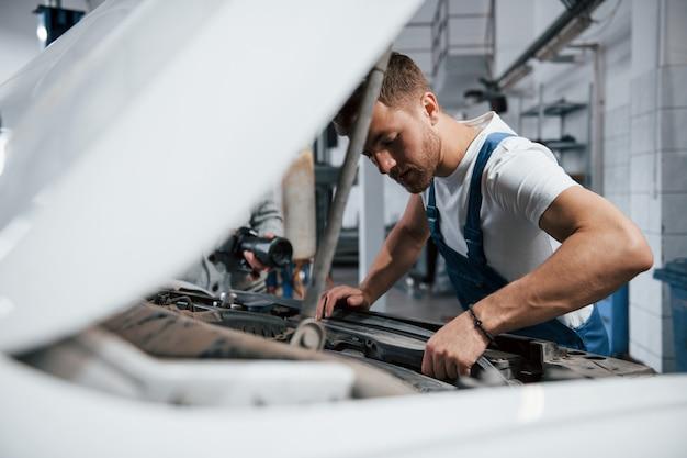 Sguardo concentrato. l'impiegato con l'uniforme di colore blu lavora nel salone dell'automobile