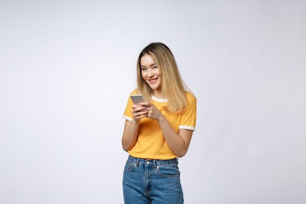Sguardo della donna e mandare un sms con l'amico sul telefono cellulare isolato sopra fondo grigio.