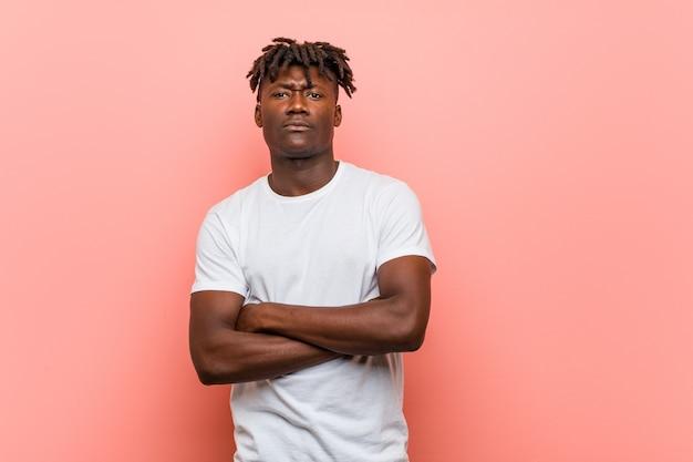 Sguardo infelice del giovane uomo di colore africano in camera con l'espressione sarcastica.