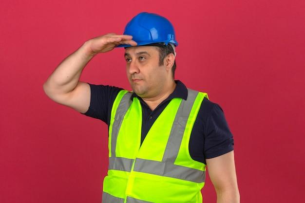Sguardo sorridente d'uso della maglia gialla della costruzione e casco di sicurezza dell'uomo invecchiato mezzo che sorride lontano con il concetto di ricerca sopraelevato della mano sopra la parete rosa isolata