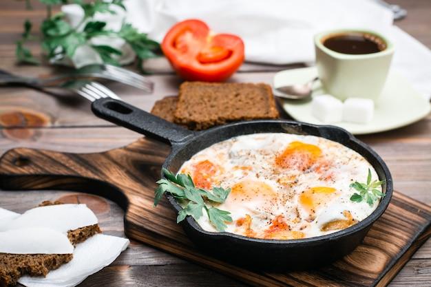 Shakshuka di uova fritte con pomodori e prezzemolo in una padella, pane con burro e caffè