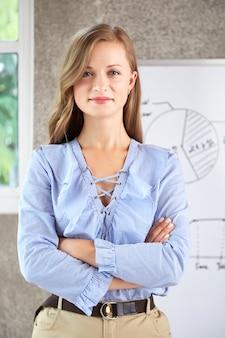Shaot medio di donna in piedi in ufficio con le mani giunte