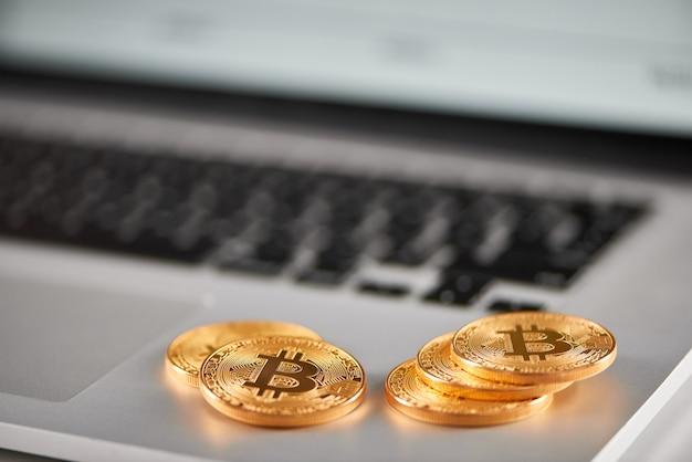 Sharp focus su bitcoins dorati posizionati sul portatile argento con grafico finanziario sfocato sul suo schermo.