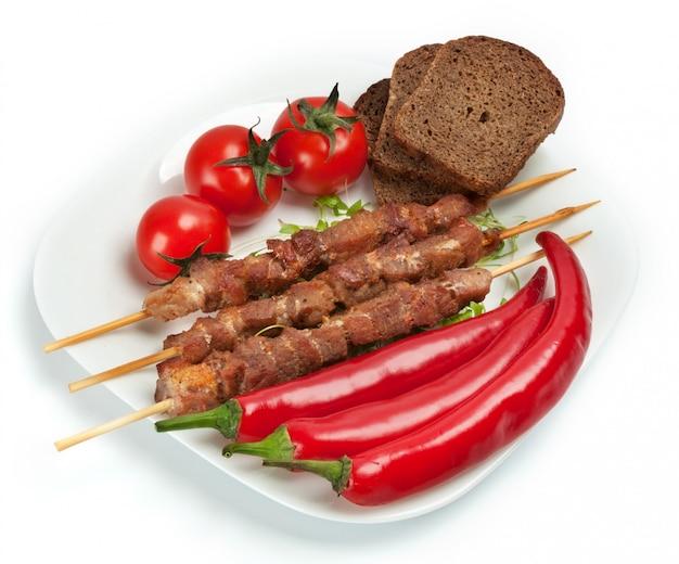 Shashlik su un piatto con pomodorini
