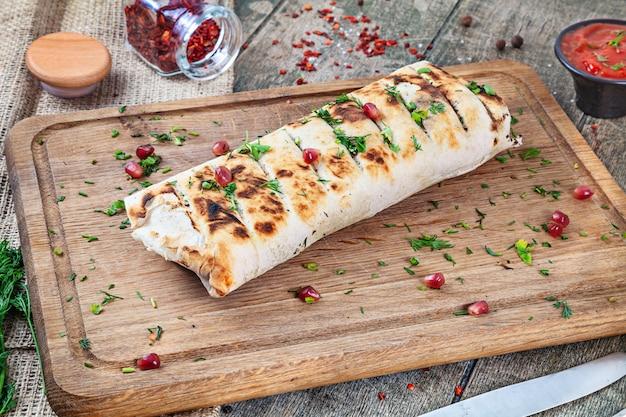 Shaurma, shawerma, kebab servito su tavola di legno con salsa. cibo vegano con falafel. cucina araba o orientale. copia spazio, messa a fuoco selettiva. shaurma con spezie, pomodorini e peperone