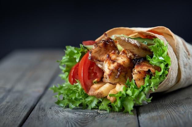 Shawarma arriva a fiumi il lavash con carne e verdure arrostite su fondo di legno