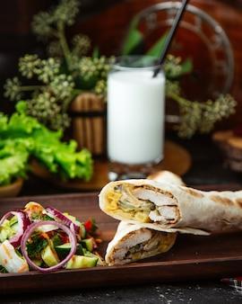 Shawarma di pollo tagliato a metà servito con insalata di verdure