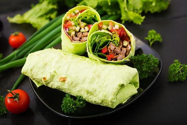 Shawarma di succosa carne di manzo, lattuga, pomodori, cetrioli, paprika e cipolla nel pane pita con spinaci. menu dietetico