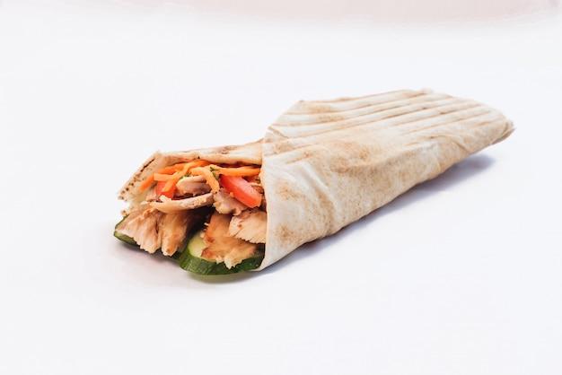 Shawarma isolato con un'ombra. cibo orientale a base di carne di pollo, pomodori, cetrioli nel pane pita
