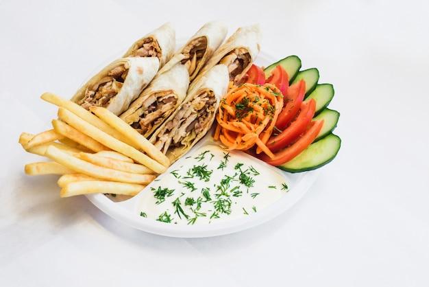 Shawarma isolato in un piatto con ombra. cibo orientale a base di carne di pollo, pomodori, carote coreane, patatine fritte, cetrioli nel pane pita