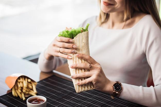 Shawarma, nelle mani di una donna. il concetto di fast food. donna graziosa che mangia patatine fritte e fajitos in un fast food. copyspace
