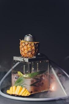 Shisha con ciotola di frutta con fumo colorato nel primo piano bar narghilè.