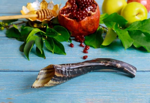 Shofar, melograno e miele con la mela sul tavolo blu. concetto di rosh hashanah.