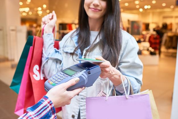 Shopaholic pagando per l'abbigliamento con lo smartphone