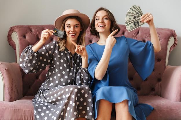 Shopaholics emozionanti delle giovani donne che tengono soldi e carta di credito.