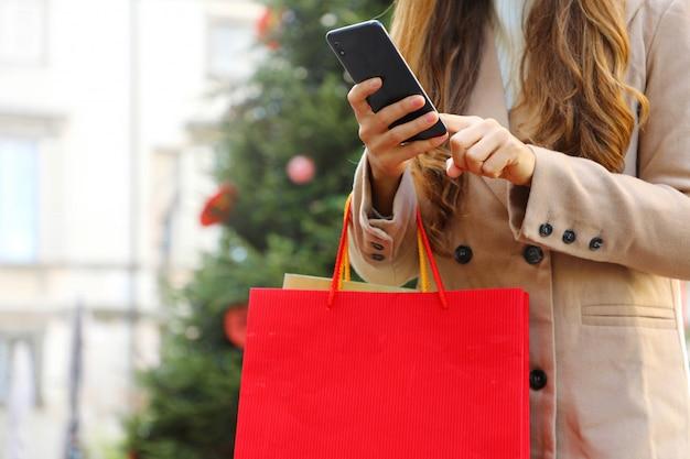 Shopper donna utilizzando smart phone per lo shopping online e il trasporto di borse nel periodo natalizio.