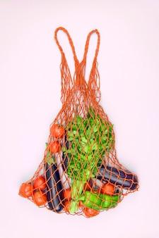 Shopping bag riutilizzabile con verdure eco su una superficie rosa. zero rifiuti, concetto privo di plastica. alimento rinfrescante di estate, concetto amichevole di eco, verticale