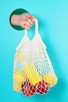 Shopping bag riutilizzabile in rete con limoni, frutta e bottiglia di vetro. zero rifiuti, concetto privo di plastica.