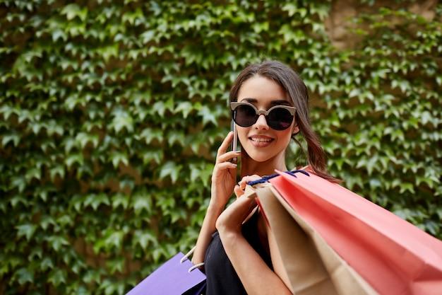 Shopping. close up ritratto di giovane attraente ragazza dalla pelle abbronzata indoeuropea in occhiali da sole e abito nero tenendo un sacco di borse dopo lo shopping, parlando al telefono con un amico, guardando a porte chiuse con un felice
